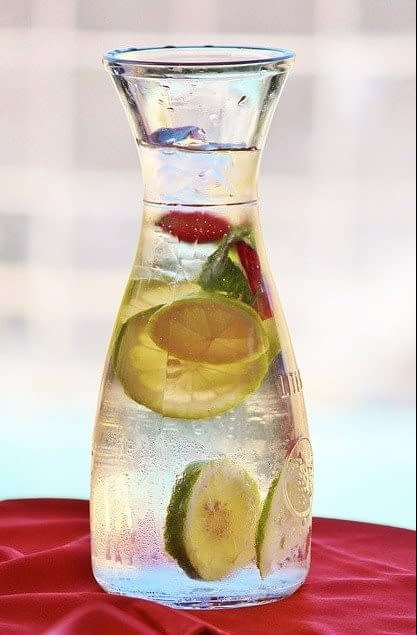 a carafe of water with lemons