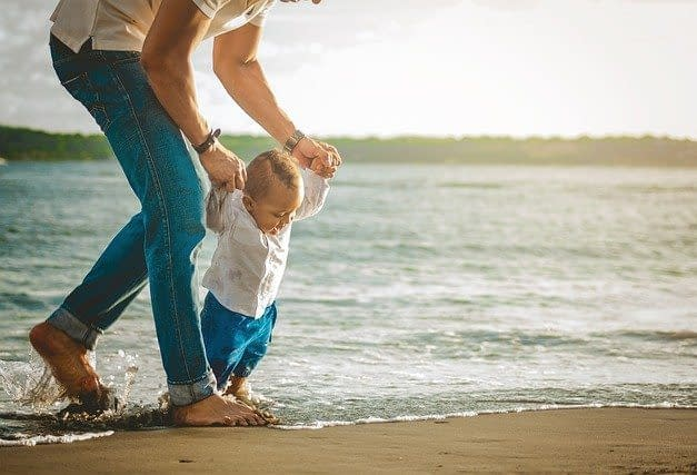 a father and his little son on the beach walking through the sea