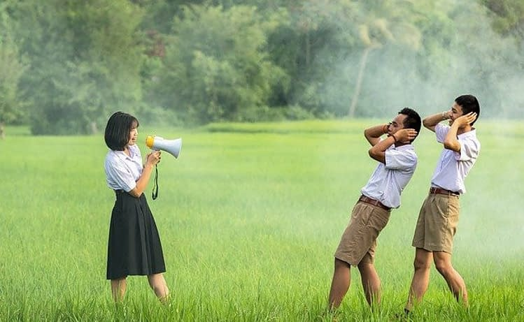 chinese woman using a megaphone sayong something to two chinese men holding close their ears