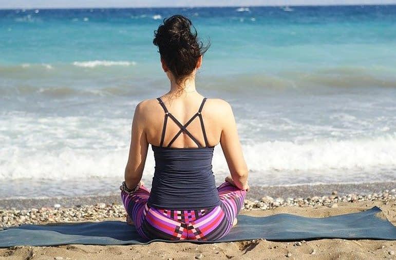 woman meditating sitting on a beach
