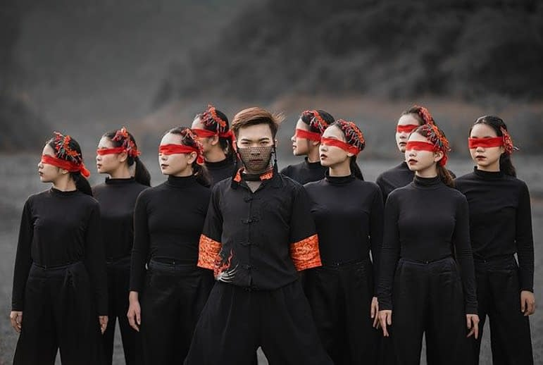 asian women covering their eyes with a organge band, and a man a net before his mouth, all dressed in black
