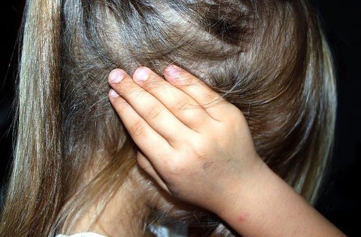 girl holding her hands on her ears