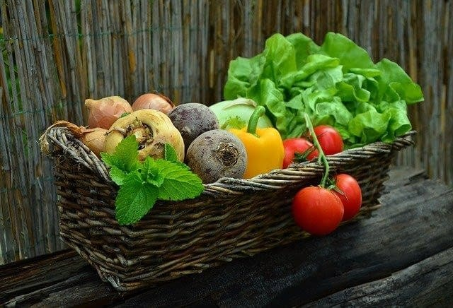 a basket with different colored vegetables