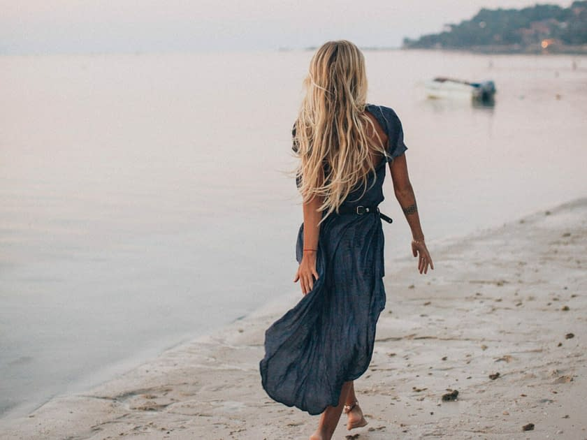 a woman with a blue dress and long blond hair walking along the beach