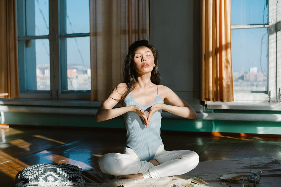 a young woman meditating in her house