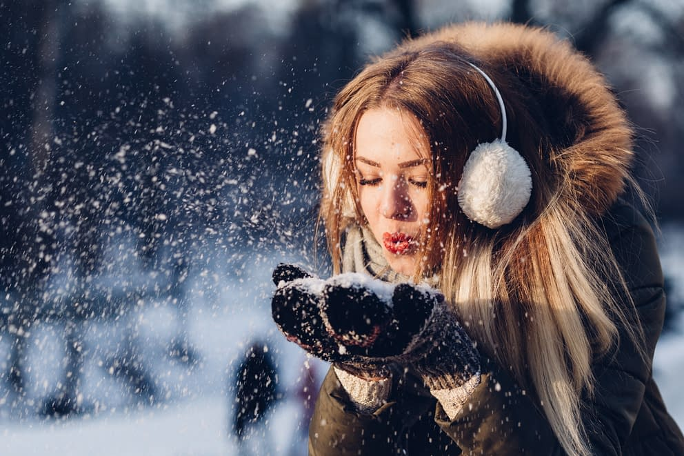 woman blowing snow from her hands