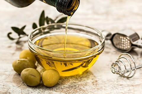olive oil in a bowl and green olives beside the bowl