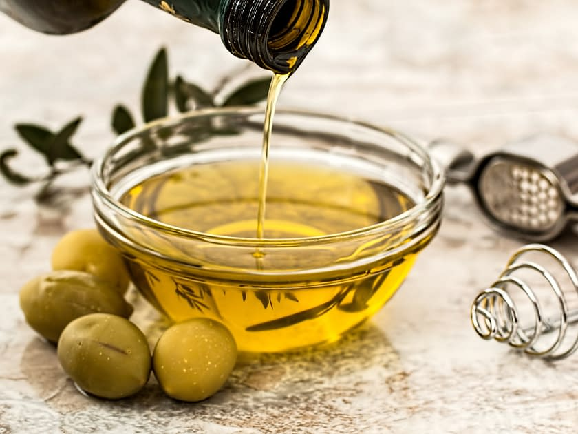 olive oil in bowl and green olives in front
