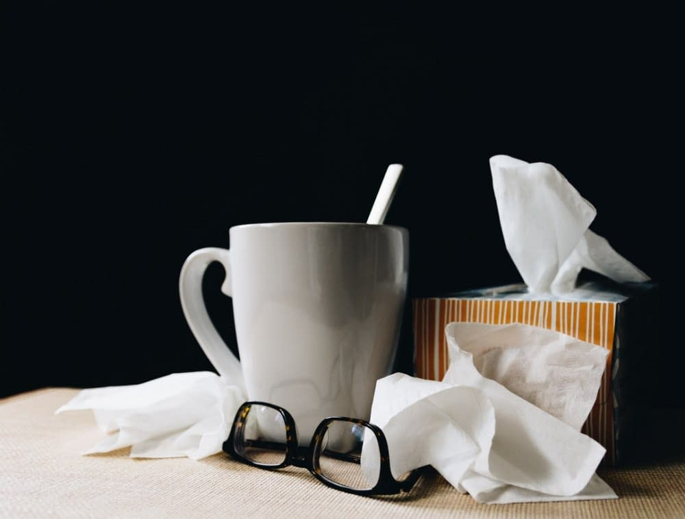 glasses, tissues and cup of tea with a spoon on a table
