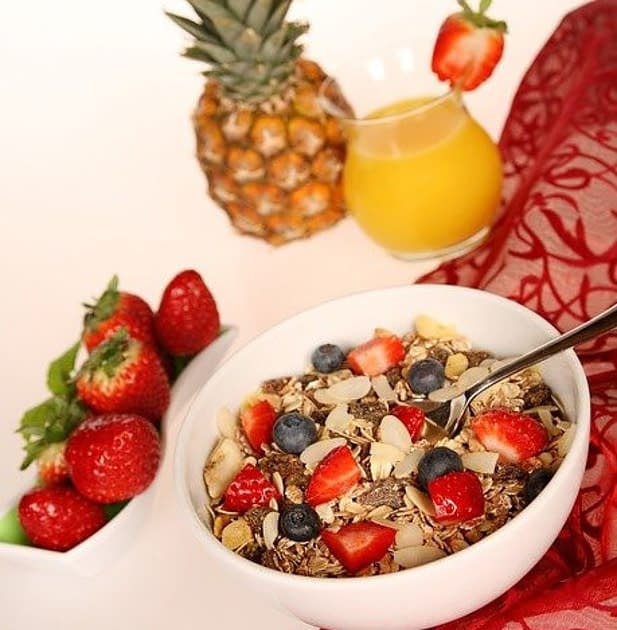 healthy food, berries, ananas, strawberries, a bowl with musli, a glass of orange