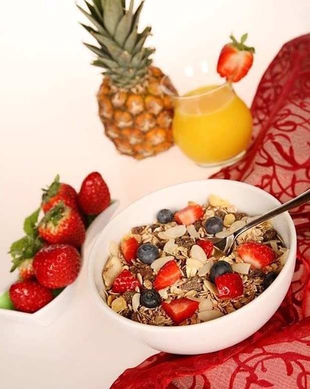 a bowl with fruit and seeds, and nuts, pineapple, strawberries, blue berries