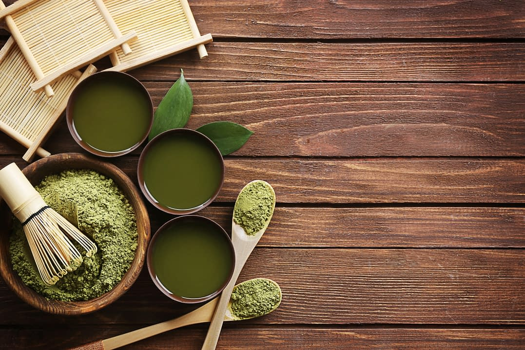 Go Green- green juice powders- Healthy Life, diferent small bowls with green powders resoved in water, two wooden spoons with green powders and a big bowl with green powders