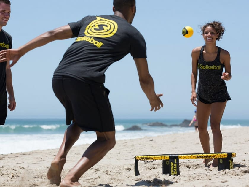 two people on the beach playing volley ball