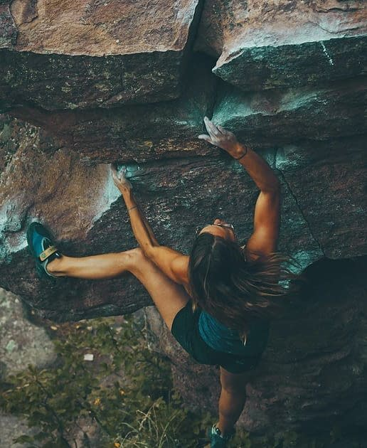 woman climbing in a wall of a mountain