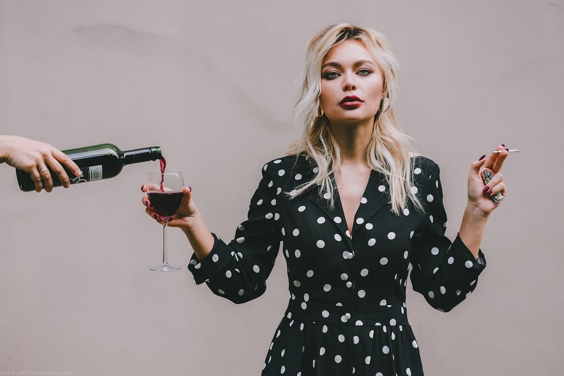 blond woman smoking and drinking red wine