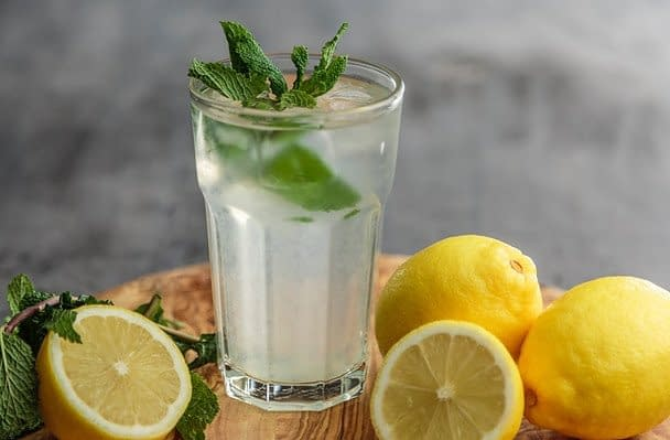 a glass of water with lemons and mint