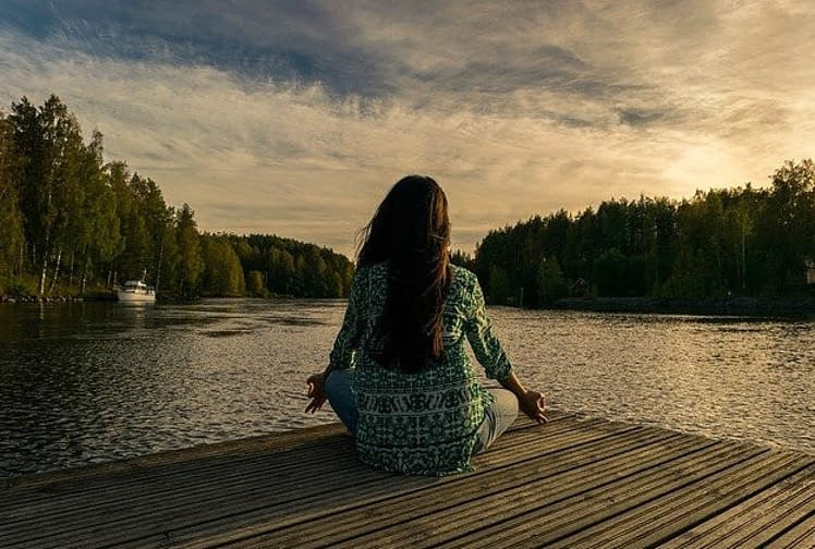 a woman meditating near a lake
