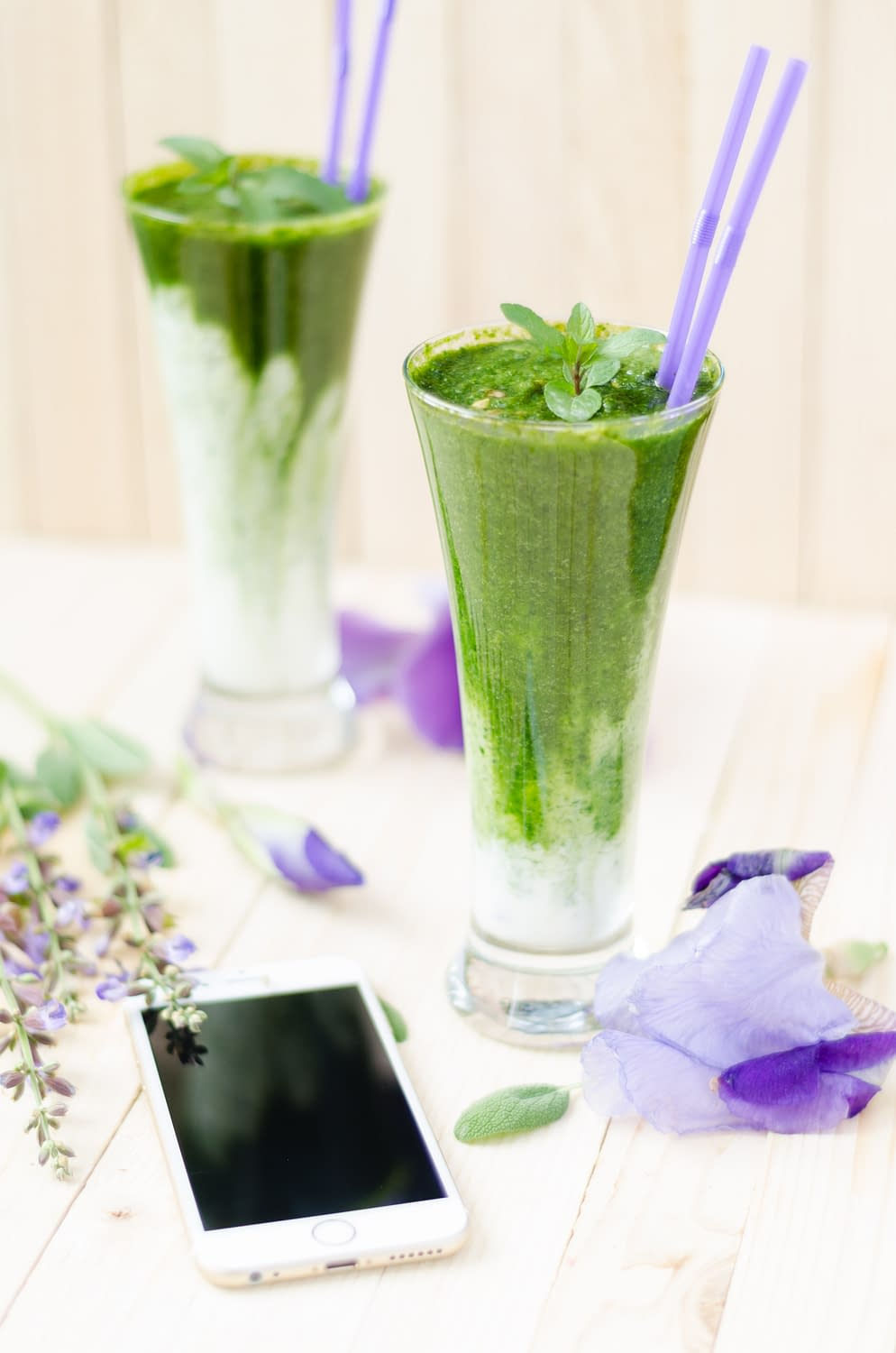 green juices in two glasses with two straws a mobile phone in the front