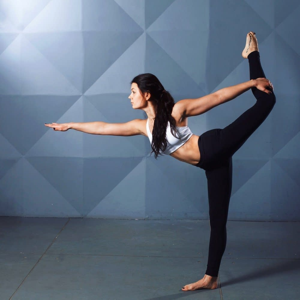 a woman with long black hair is doing yoga